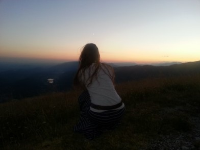 Jess taking photos of the sunset while on top of a mountain peak in the Dolomites, Italy. Photo taken by Trina Otero.